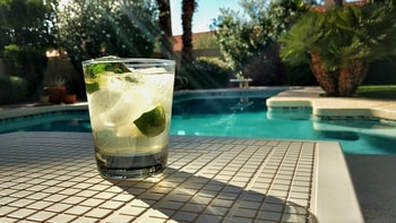 Picture of a cocktail with clear liquor, a lime and muddled mint with ice in front of a pool beautiful pool.  Looks like a summertime delight.