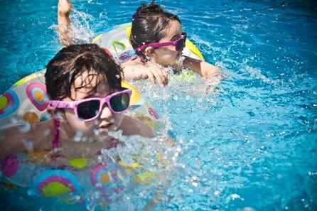 Photograph of two baby girls swimming next to each other in a pool with matching swimmer tubes.  Both are wearing pink sunglasses and splashing the water.