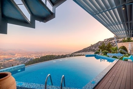 Picture of modern infinity pool overlooking a vast valley.  It is taken at sundown with the sun setting over the hill beside the pool.  The water is gorgeous and looks as if it's spilling into the valley.