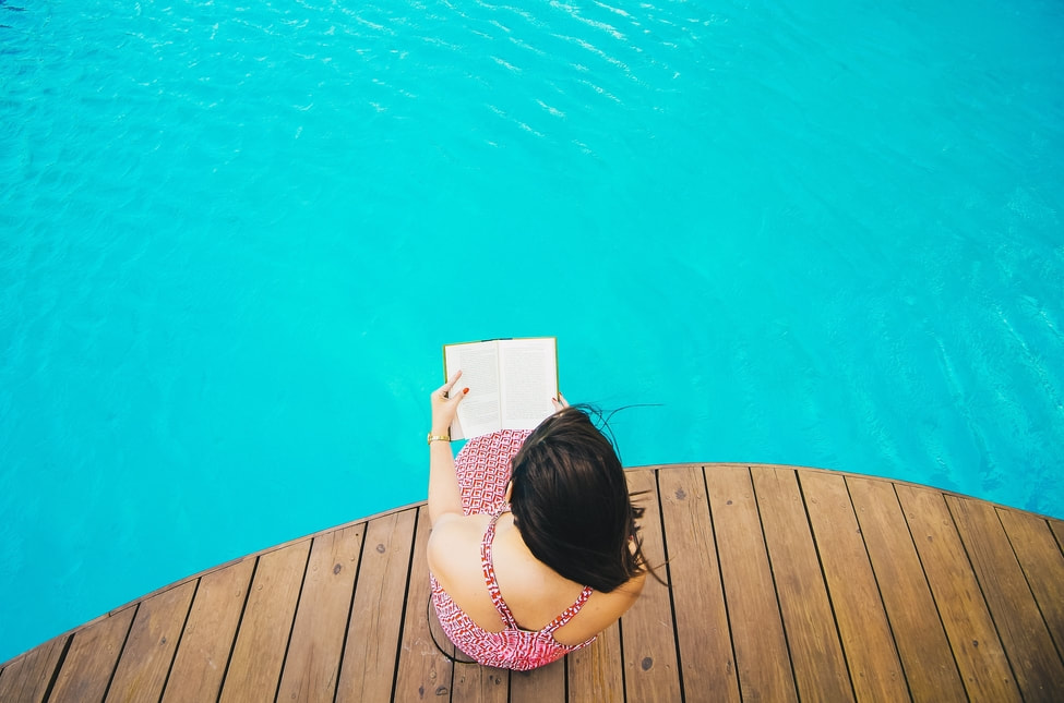 Ariel picture of young woman reading by swimming pool, her back turned and feet handing in the water.  The pool deck is brown wood and pool is aqua blue.